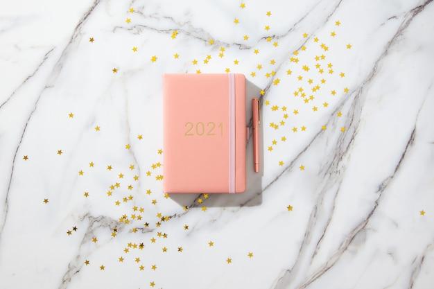 Notebook con pagine vuote per il testo, con penna, tazza di caffè, scatole regalo, scintillii d'oro sulla scrivania bianca