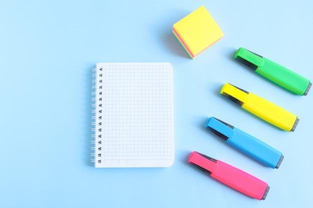 Un quaderno con una pagina bianca vuota e cancelleria di colori vivaci su sfondo blu