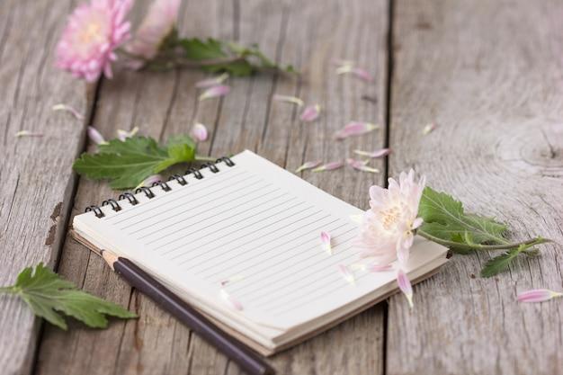 Quaderno con fiori sul tavolo di legno
