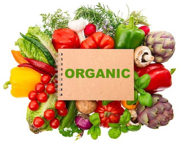 Notebook con verdure biologiche fresche ed erbe aromatiche isolate su sfondo bianco. cibo crudo. ingredienti per una sana alimentazione. ricettario con testo di esempio biologico