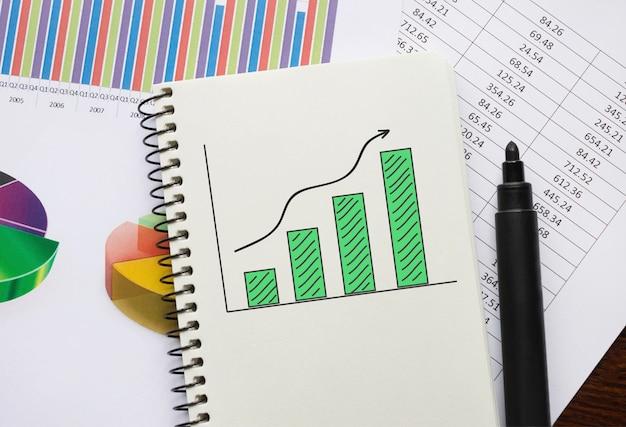 Notebook con grafico e linea di aumento, concetto di affari