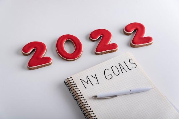 Notebook con iscrizione i miei obiettivi, penna e numeri 2022 su sfondo bianco. avvicinamento.