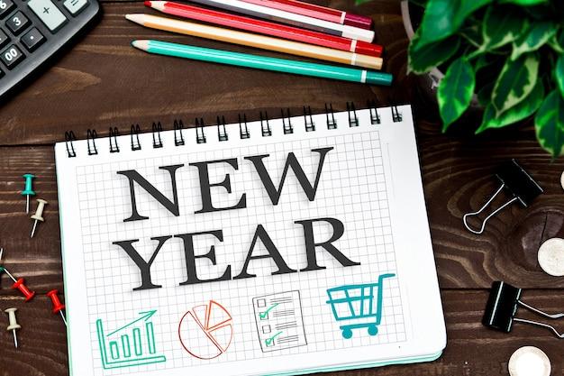Taccuino con le note nuovo anno sulla tavola dell'ufficio con gli strumenti.