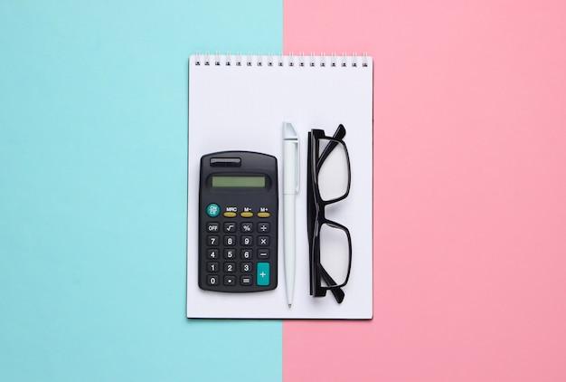 Taccuino con penna, calcolatrice e bicchieri su pastello blu rosa.