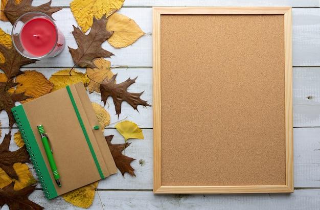 Notebook con penna, bacheca di sughero sulla tavola di legno con foglie di albero. lay piatto