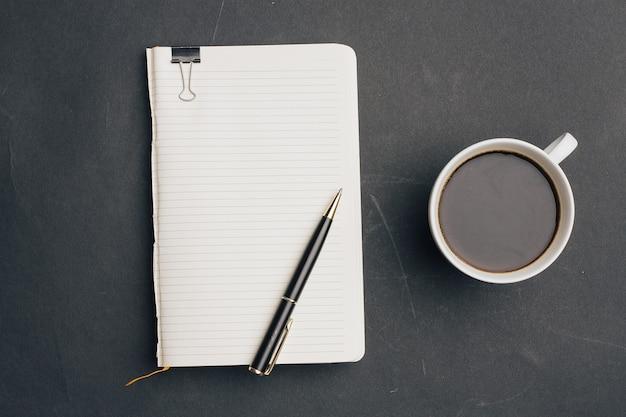 Notebook con penna su sfondo scuro e tazza di caffè vista dall'alto dell'ufficio