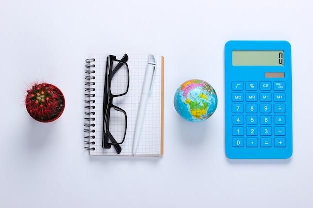 Taccuino con penna, occhiali, cactus, globo, calcolatrice su bianco. spazio di lavoro