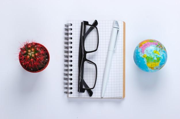 Taccuino con penna, occhiali, cactus, globo su bianco. spazio di lavoro