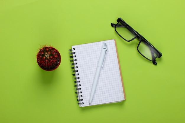 Taccuino con penna, occhiali, cactus su un verde. spazio di lavoro