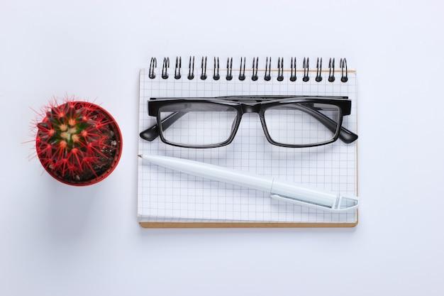 Taccuino con penna, occhiali, cactus su bianco. spazio di lavoro