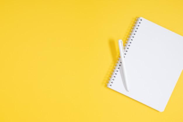 Taccuino con penna su sfondo giallo vista dall'alto piatta