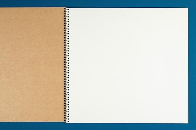 Taccuino con la matita sulla vista superiore della parete blu, scolaro che fa i compiti, scrivania del lavoratore di ufficio laici piana. blocco note vuoto sul tavolo
