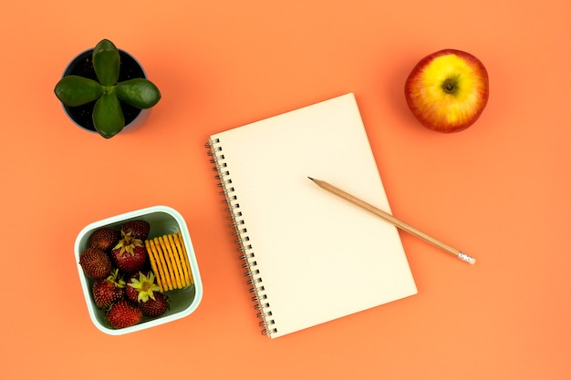 Taccuino con matita casa fiore e contenitore con fragole e biscotti su sfondo arancione