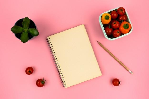 Taccuino con matita casa fiore e contenitore con verdure su sfondo rosa vista dall'alto