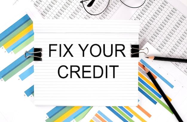 Taccuino con matite, occhiali sulla superficie del grafico, con testo fix your credit