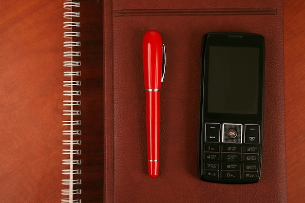 Il taccuino con la penna rossa e il cellulare sono sul tavolo