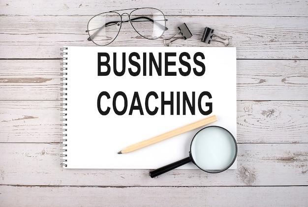 Taccuino con testo business coaching sul tavolo di legno con penna, lente d'ingrandimento e occhiali