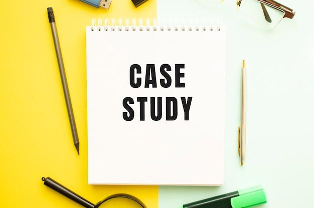 Notebook con testo case study sul tavolo da ufficio con forniture per ufficio sfondo di colore giallo