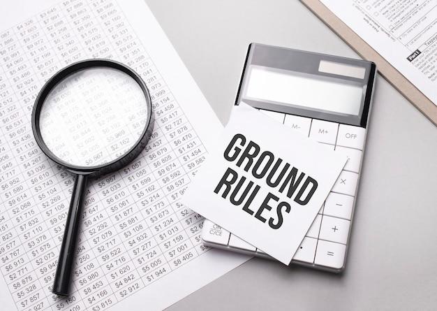 Notebook con testo regole di terra foglio di carta bianca per appunti, calcolatrice, lente d'ingrandimento.