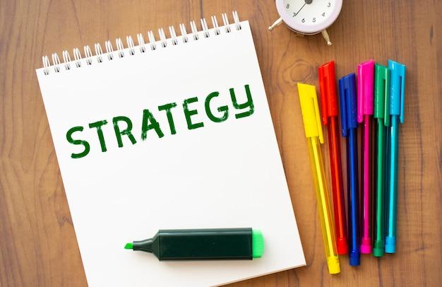 Un taccuino con il testo strategia su un foglio bianco giace su un tavolo di legno marrone con penne colorate