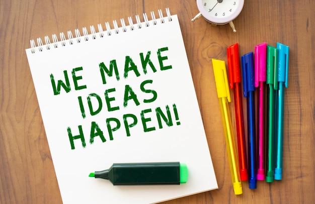 Un quaderno con il testo we fare idee succede su un foglio bianco giace su un tavolo di legno marrone con penne colorate
