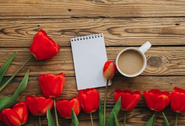Notebook con pagine bianche, tulipani rossi e tazza di caffè sullo sfondo di legno.