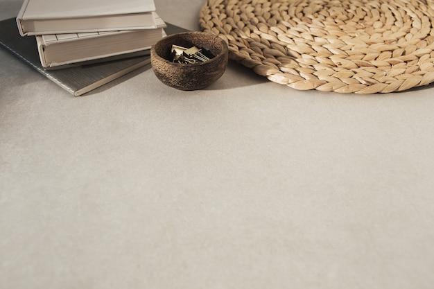 Notebook, clip in una ciotola di legno, supporto di paglia su cemento beige