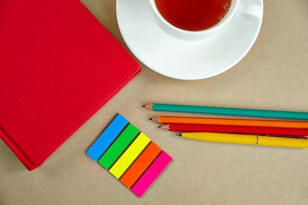 Quaderni, penne, matite, segnalibri tazza di tè, su uno sfondo di carta, close-up