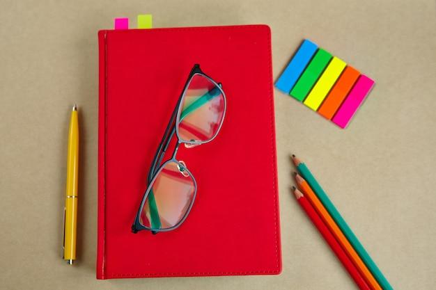 Quaderni, penne, matite, bicchieri, segnalibri, su uno sfondo di carta