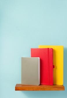 Blocco note e libro sullo scaffale sulla superficie dello sfondo della parete