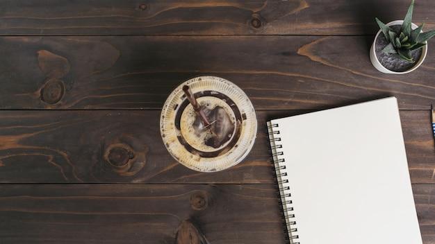 Blocco note e tazza di caffè sulla tavola di legno con lo spazio della copia