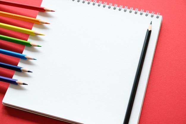 Blocco note e matite colorate su un rosso
