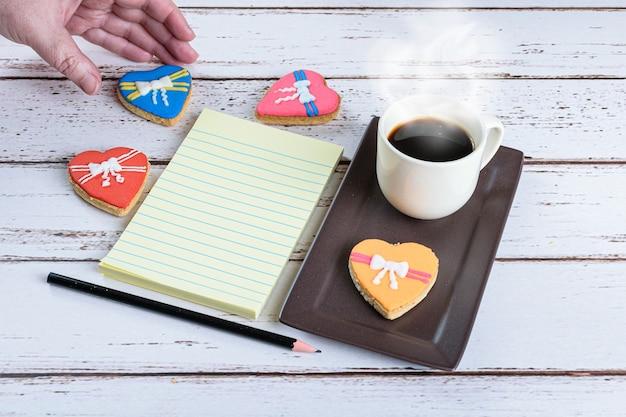 Blocco note accanto a una tazza di caffè, una matita e una donna che prende in mano un biscotto.