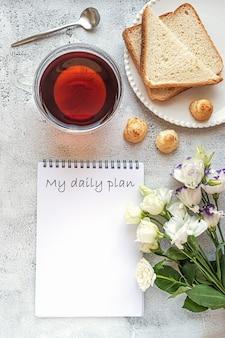 Un blocco note per la pianificazione quotidiana con colazione e fiori