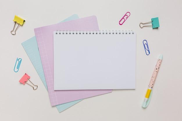 Blocco note, quaderno e penna sulla scrivania. mock up in ufficio spazio copia su sfondo bianco. di nuovo a scuola