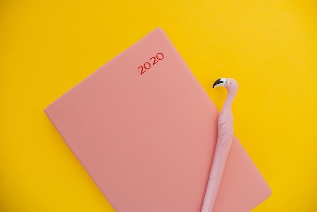 Blocchetto per appunti e penna del fenicottero su una priorità bassa astratta gialla con lo spazio della copia,