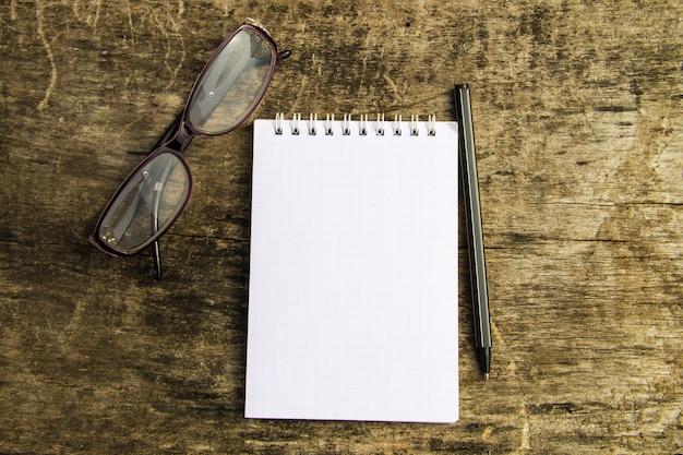 Blocco note, occhiali e penna sulla vecchia scrivania in legno. vista dall'alto
