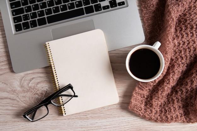 Tazza del blocco note, del computer portatile e di caffè sulla tavola di legno