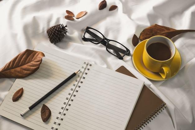 Tazza di caffè della lettera del blocco note e un libro con una coperta su una tessile bianca a letto.