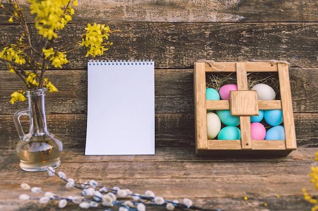Modello di blocco note con uova di pasqua e fiori. sullo sfondo di una vecchia tavola.