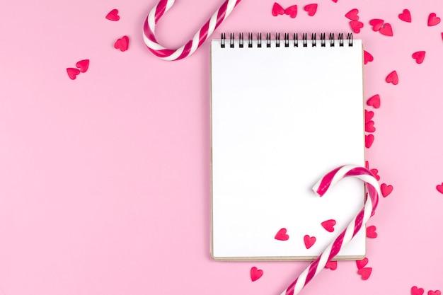 Pagina del blocco note, cuori rossi e bastoncini di zucchero su uno spazio rosa della copia della parete.