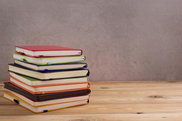 Blocco note o taccuino di carta al tavolo di legno della superficie del fondo del tavolo
