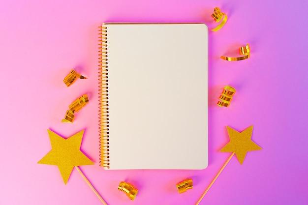 Carta del blocco note con nastri dorati e stelle dorate sulla superficie rosa