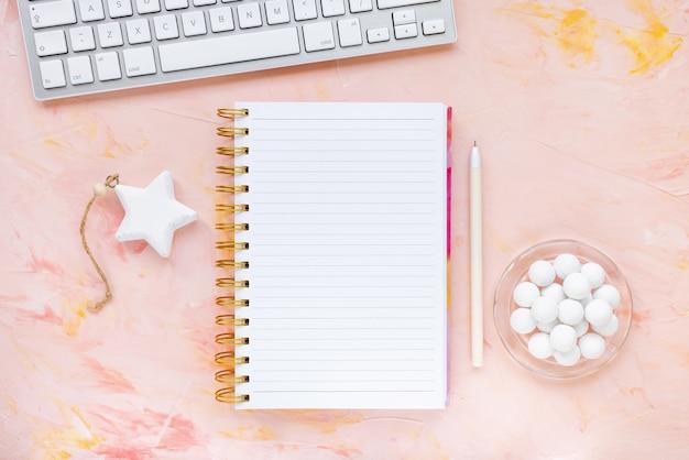 Blocco note, penna, tastiera del computer, orologio, cioccolato sull'area di lavoro della scrivania