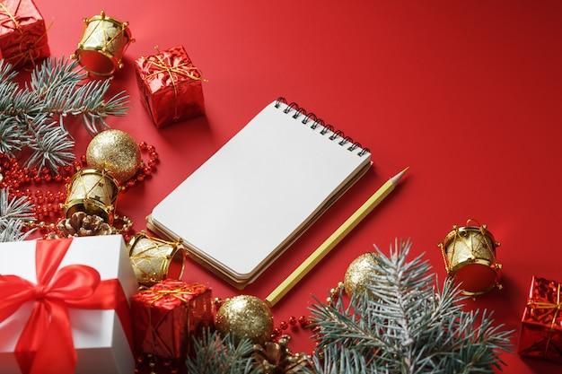 Blocco note e matita per scrivere auguri e regali per il nuovo anno e il natale intorno alle decorazioni dell'albero di natale