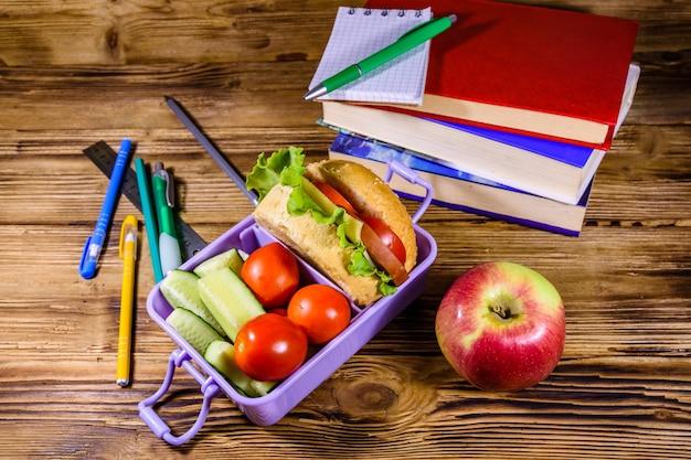 Blocco note, penne, mela matura, pila di libri e scatola per il pranzo con hamburger, cetrioli e pomodori su tavola in legno rustico