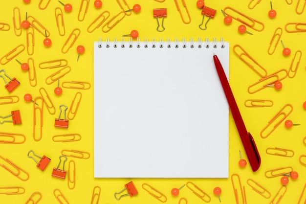 Blocco note e penna rossa su uno sfondo di carta gialla. apra il taccuino e le forniture sul tavolo.