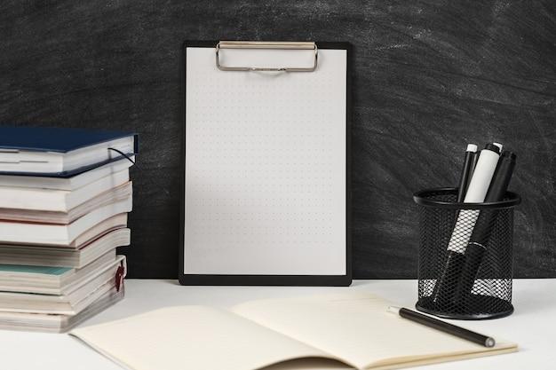 Blocco note sulla lavagna della scuola con forniture per ufficio