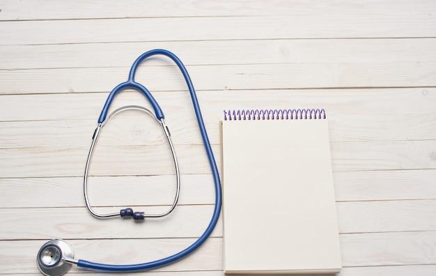 Blocco note e stetoscopio su una struttura di immagine di sfondo di tavolo in legno. foto di alta qualità