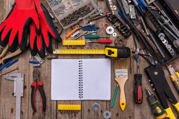 Blocco note circondato da strumenti polverosi su una vecchia superficie di legno